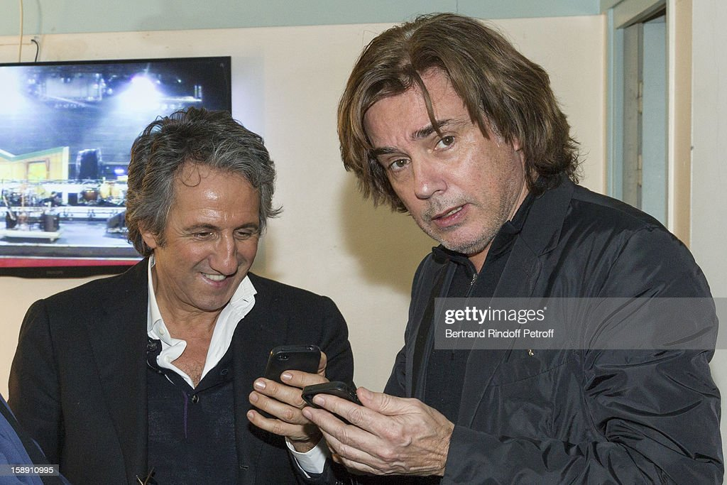 Jean-Michel Jarre (R) and Richard Anconina pose in the dressing room of French impersonator Laurent Gerra following Gerra's one man show at Olympia hall on December 28, 2012 in Paris, France.