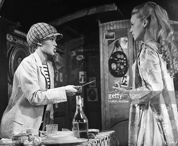 Jeanne Moreau holds a knife to Brigitte Bardot in a scene for the movie 'Viva Maria' circa 1965