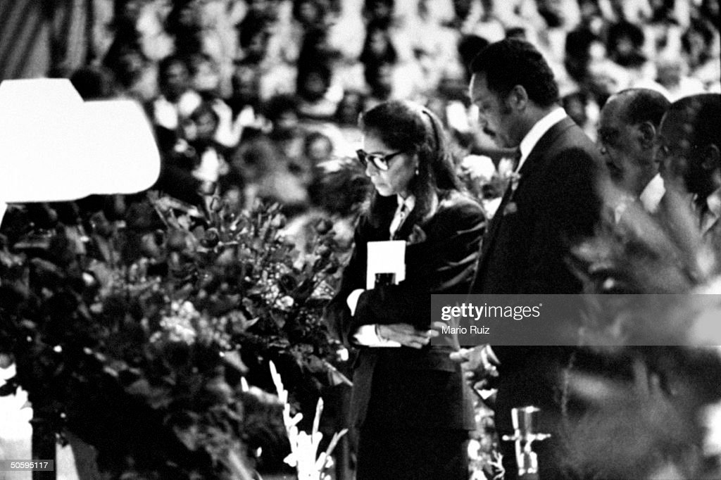 Jeanne Moutoussamy, wife of tennis great/AIDS victim Arthur Ashe, w. Jesse Jackson & others paying last respects at Ashe's flower covered coffin during his funeral.
