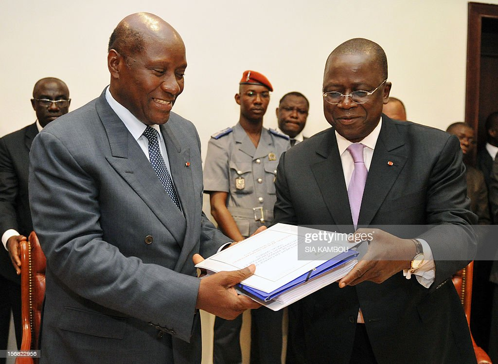 Jeannot Kouadio Ahoussou (r) outgoing prime minister and new premier Daniel Kablan Duncan (l) exchange documents during the handover on November 22, 2012 in Abidjan .The 69-year-old, a member of former president Henri Konan Bedie's PDCI party, was named to succeed Ahoussou after Ouattara dissolved the government on November 14.