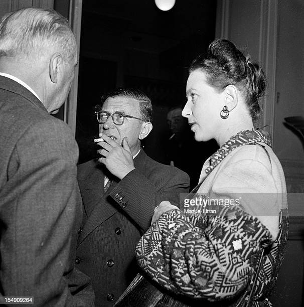 JeanPaul Sartre smoking a cigarette and Simone de Beauvoir talking with an unidentified person