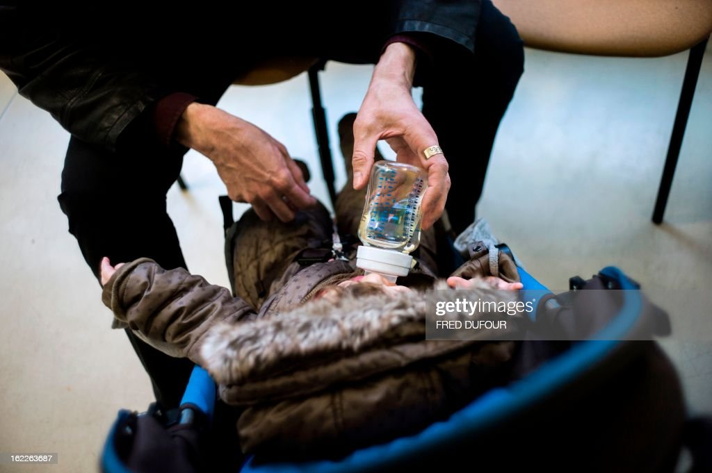 Jean-Philippe, a father of a 10 month-old daughter, gives water to the baby in a child care center, on February 20, 2013 in Paris. Recently separated with the child's mother, he is waiting for the court to decide whether he will be granted half-time custody of the child.