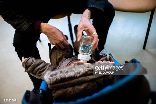JeanPhilippe a father of a 10 monthold daughter gives water to the baby in a child care center on February 20 2013 in Paris Recently separated with...