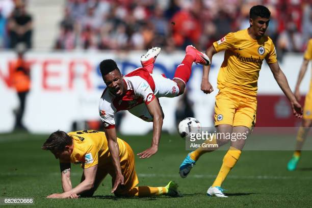 JeanPhilippe Gbamin of Mainz is challenged by Bastian Oczipka and Aymane Barkok of Frankfurt during the Bundesliga match between 1 FSV Mainz 05 and...