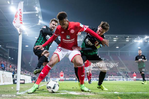 JeanPhilippe Gbamin of Mainz is challenged by Paul Verhaegh and Daniel Baier of Augsburg during the Bundesliga match between 1 FSV Mainz 05 and FC...