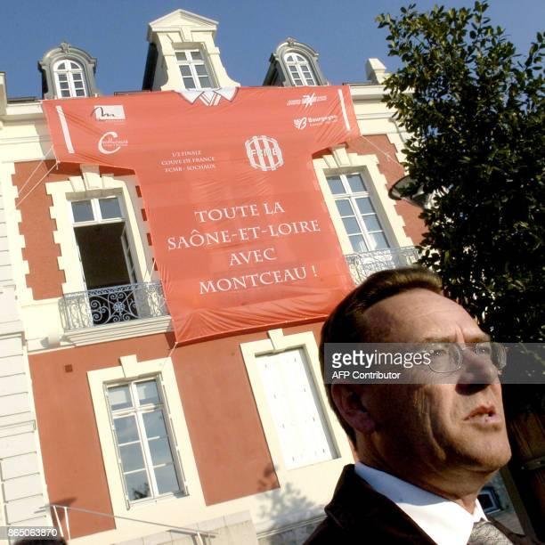 JeanPierre Bailly président du club de football de MontceauLesMines pose devant l'hôtel de ville sur la façade duquel un maillot du club a été étendu...