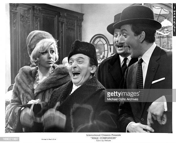 JeanPierre Cassel laughing with Marcel Dalio as Catherine Deneuve stands not amused in a scene from the film 'Male Companion' 1964