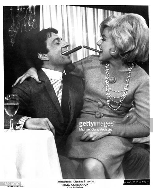 JeanPierre Cassel with a cigar in his mouth and Catherine Deneuve on his lap as she enjoys a cigar of her own in a scene from the film 'Male...