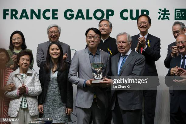 JeanPierre Colombu VicePresident of France Galop presents the trophy to the winning owner Ronald Ma Chun Ho at Happy Valley Racecourse on May 17 2017...
