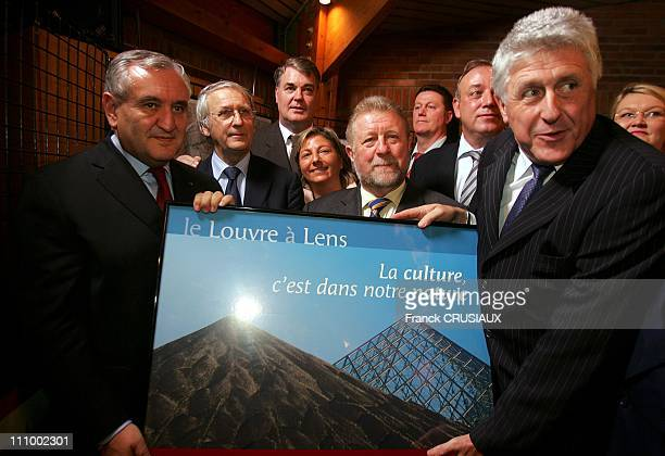 JeanPierre Raffarin and Guy Delcourt mayor of Lens right of photo pose with the poster of the Louvre project in the visit of Prime Minister...