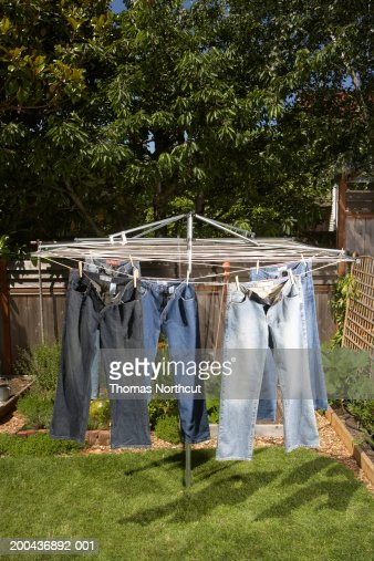 Jeans hanging from clothesline outdoors, elevated view : Stock Photo