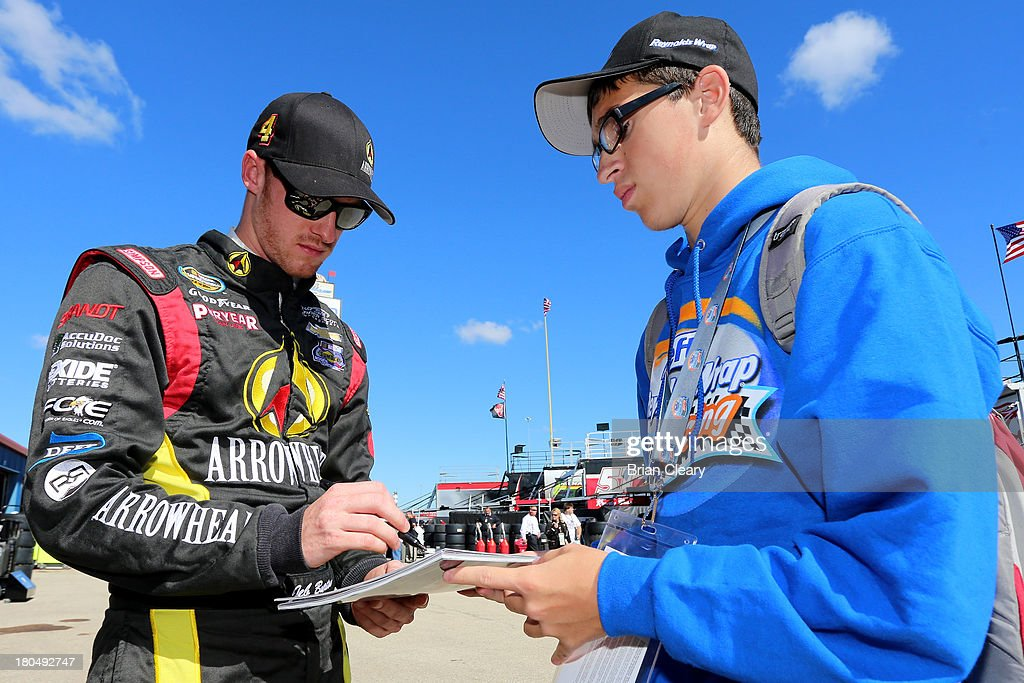 Jeb Burton, driver of the #4 Arrowhead Chevrolet, signs autographs during practice for the NASCAR Camping World Truck Series enjoyillinois.com 225 at Chicagoland Speedway on September 13, 2013 in Joliet, Illinois.