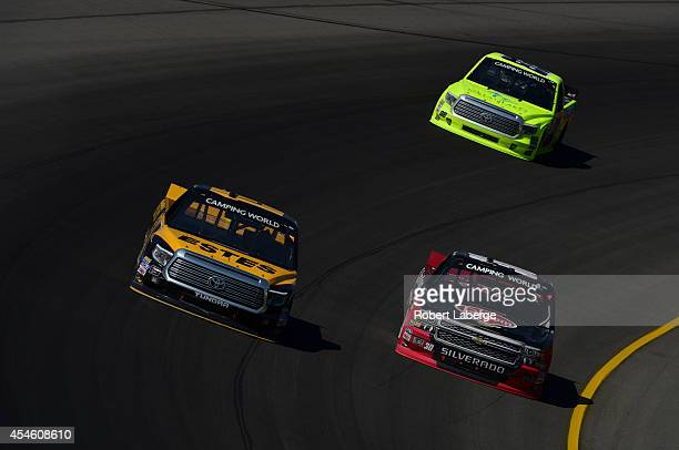 Jeb Burton driver of the EstesCarolina Nut Company Toyota races with Ron Hornaday Jr driver of the Rheem Chevrolet during the NASCAR Camping World...