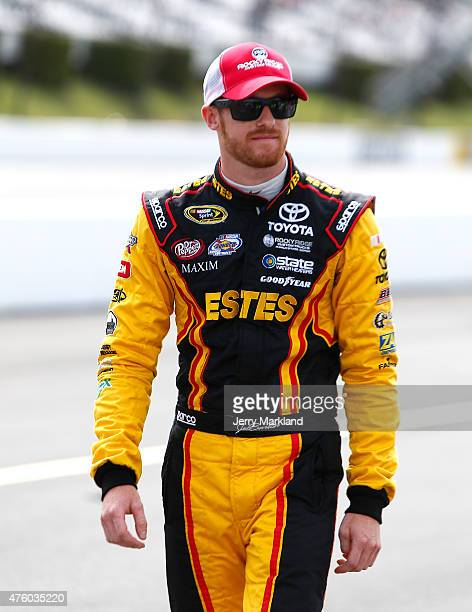 Jeb Burton driver of the Maxim Fantasy Sports Toyota walks on the grid prior to qualifying for the NASCAR Sprint Cup Series Axalta 'We Paint Winners'...