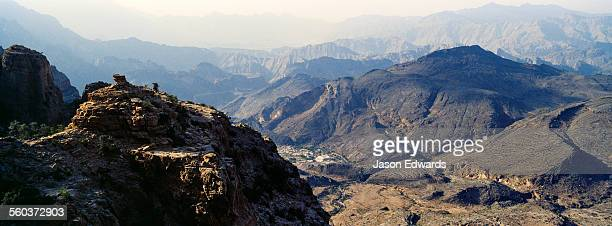 The steep slopes of arid jagged mountains overlooking an eroded and inhospitable rocky desert valley.
