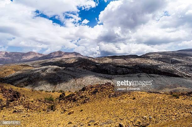 The arid rocky slopes of a prehistoric and volcanic desert landscape.
