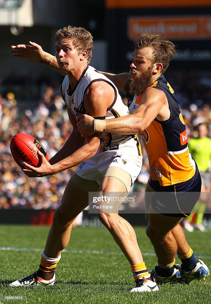 Jed Anderson of the Hawks gets tackled by Will Schofield of the Eagles during the round two AFL match between the West Coast Eagles and the Hawthorn Hawks at Patersons Stadium on April 7, 2013 in Perth, Australia.
