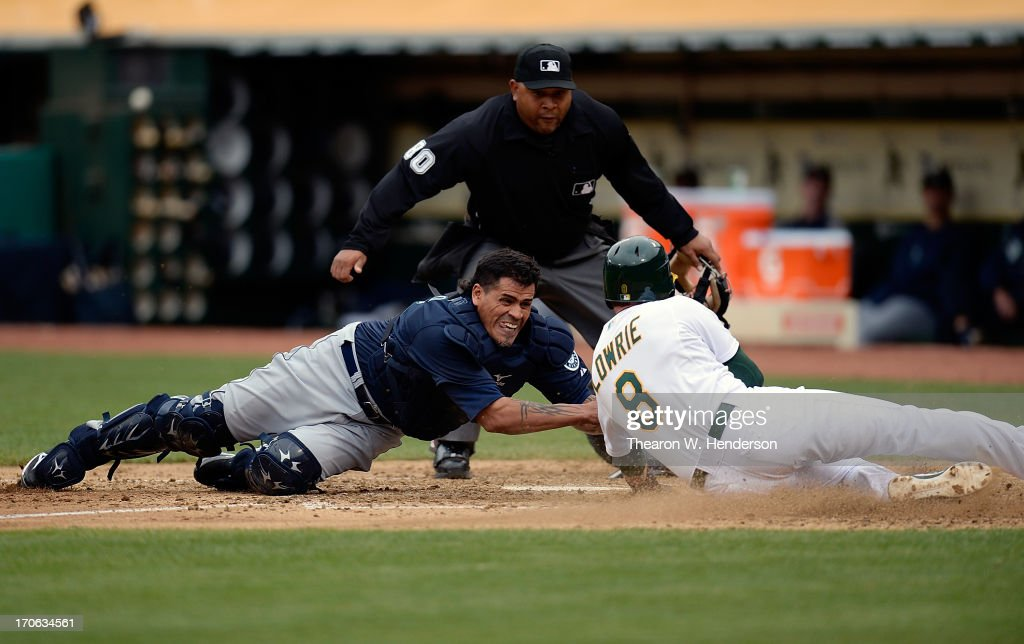 <a gi-track='captionPersonalityLinkClicked' href=/galleries/search?phrase=Jed+Lowrie&family=editorial&specificpeople=4949369 ng-click='$event.stopPropagation()'>Jed Lowrie</a> #8 of the Oakland Athletics attempting to score on a fly ball to right field, is tagged out at home plate by <a gi-track='captionPersonalityLinkClicked' href=/galleries/search?phrase=Henry+Blanco&family=editorial&specificpeople=211366 ng-click='$event.stopPropagation()'>Henry Blanco</a> #33 of the Seattle Mariners in the fifth inning at O.co Coliseum on June 15, 2013 in Oakland, California.