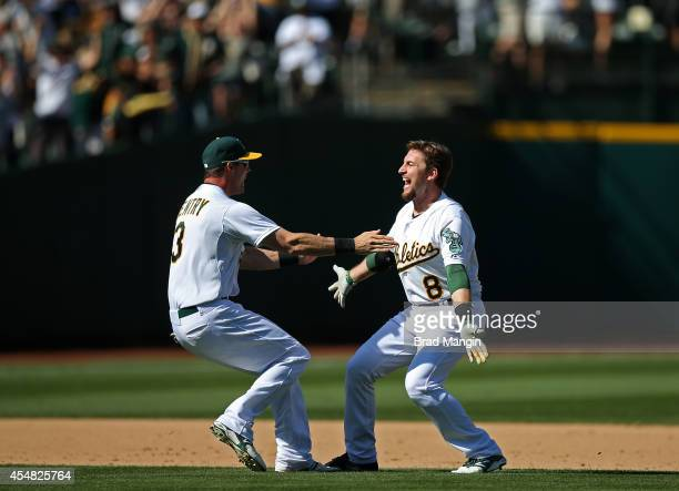 Jed Lowrie of the Oakland Athletics celebrates with teammate Craig Gentry after Lowrie drove in the winning run with a single in the bottom of the...