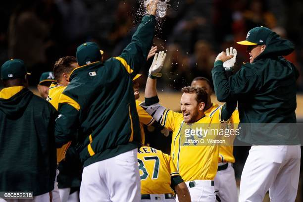 Jed Lowrie of the Oakland Athletics celebrates with teammates after hitting a walkoff home run during the eleventh inning against the Los Angeles...