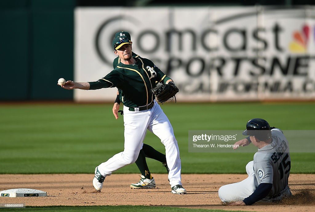 <a gi-track='captionPersonalityLinkClicked' href=/galleries/search?phrase=Jed+Lowrie&family=editorial&specificpeople=4949369 ng-click='$event.stopPropagation()'>Jed Lowrie</a> #8 of the Oakland Athletics completes the double-play over the top of <a gi-track='captionPersonalityLinkClicked' href=/galleries/search?phrase=Kyle+Seager&family=editorial&specificpeople=7682389 ng-click='$event.stopPropagation()'>Kyle Seager</a> #15 of the Seattle Mariners in the top of the seventh inning during game two of a doubleheader at O.co Coliseum on May 7, 2014 in Oakland, California. The Athletics won the game 2-0.