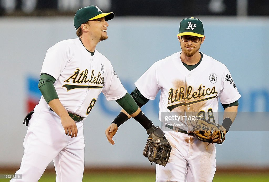 Jed Lowrie #8 of the Oakland Athletics congratulates Eric Sogard #28 of the Oakland Athletics after Sogard flipped the ball to Lowrie who then threw out Jesus Montero #63 of the Seattle Mariners at first base in the second inning during Opening Day at O.co Coliseum on April 1, 2013 in Oakland, California.