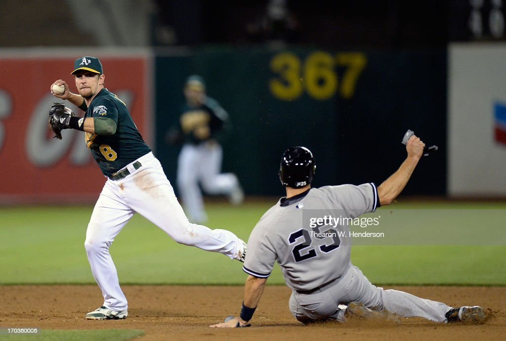 <a gi-track='captionPersonalityLinkClicked' href=/galleries/search?phrase=Jed+Lowrie&family=editorial&specificpeople=4949369 ng-click='$event.stopPropagation()'>Jed Lowrie</a> #8 of the Oakland Athletics did not get his throw off in time to complete the double-play, while avoiding the slide of <a gi-track='captionPersonalityLinkClicked' href=/galleries/search?phrase=Mark+Teixeira&family=editorial&specificpeople=209239 ng-click='$event.stopPropagation()'>Mark Teixeira</a> #25 of the New York Yankees in the eighth inning at O.co Coliseum on June 11, 2013 in Oakland, California.
