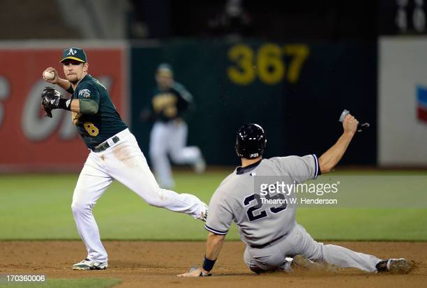 Jed Lowrie of the Oakland Athletics did not get his throw off in time to complete the doubleplay while avoiding the slide of Mark Teixeira of the New...