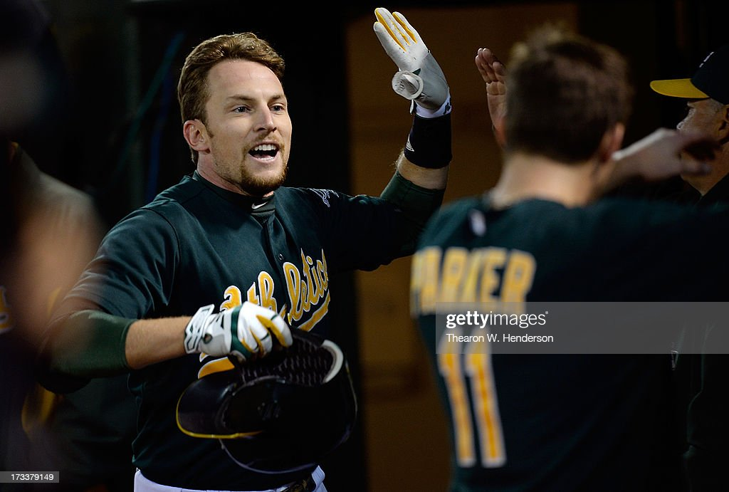 Jed Lowrie #8 of the Oakland Athletics is congratulated by teammates after hitting a solo home run in the six inning against the Boston Red Sox at O.co Coliseum on July 12, 2013 in Oakland, California.