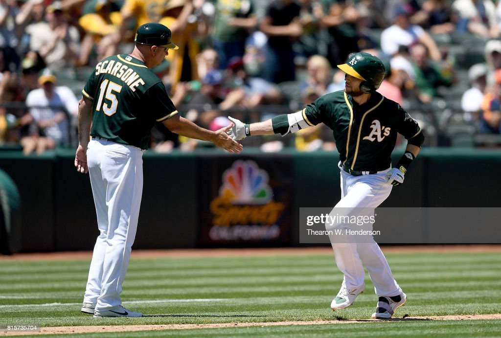 Jed Lowrie #8 of the Oakland Athletics is congratulated by third base coach Steve Scarsone #15 after Lowrie hit a solo home run against the Cleveland Indians in the bottom of the third inning at Oakland Alameda Coliseum on July 16, 2017 in Oakland, California.
