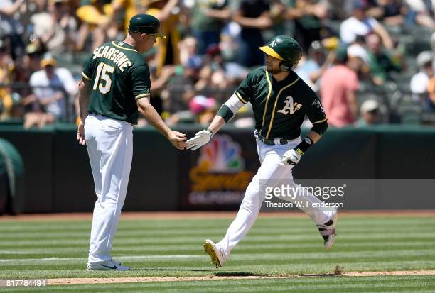 Jed Lowrie of the Oakland Athletics is congratulated by third base coach Steve Scarsone after Lowrie hit a solo home run against the Cleveland...