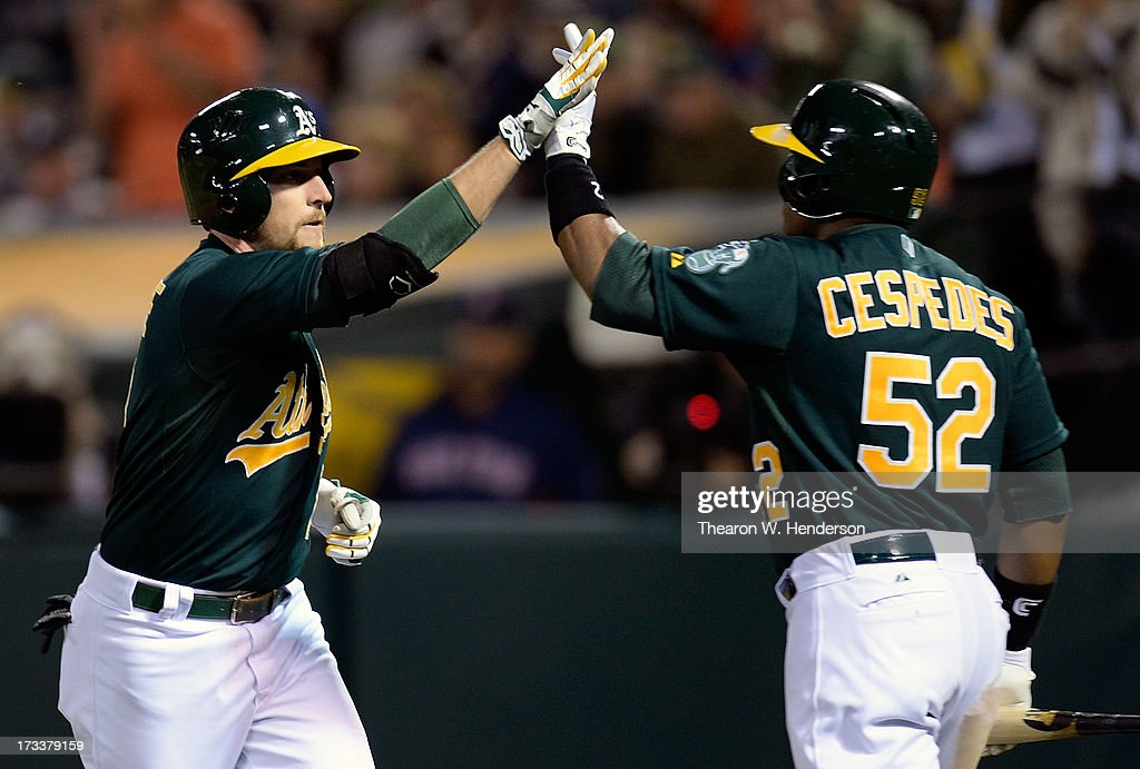 Jed Lowrie #8 of the Oakland Athletics is congratulated by Yoenis Cespedes #52 after hitting a solo home run in the six inning against the Boston Red Sox at O.co Coliseum on July 12, 2013 in Oakland, California.