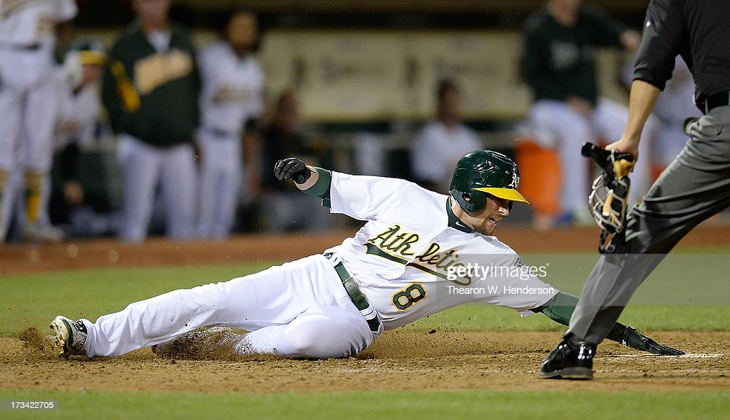 Jed Lowrie #8 of the Oakland Athletics scores on an RBI single from teammate Yoenis Cespedes #52 in the sixth inning against the Boston Red Sox at O.co Coliseum on July 13, 2013 in Oakland, California.
