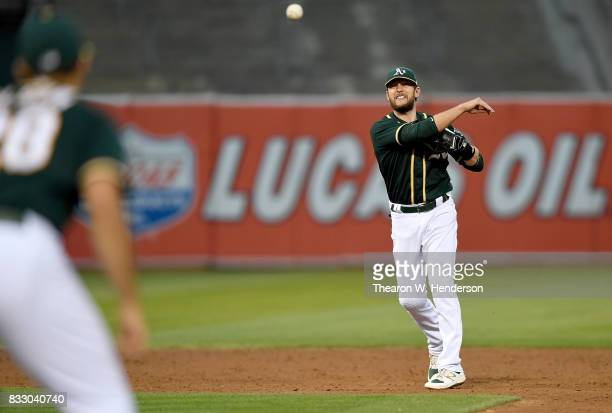 Jed Lowrie of the Oakland Athletics throws to first base to complete the double play against the Baltimore Orioles in the top of the six inning at...