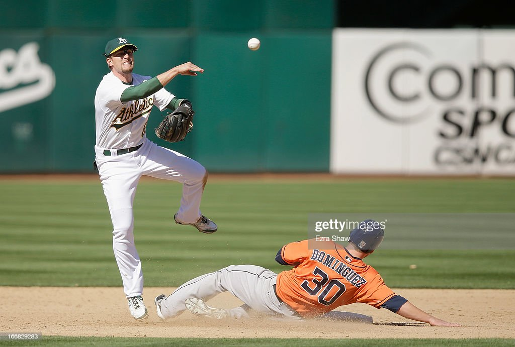 Jed Lowrie #8 of the Oakland Athletics tries to turn a double play as Matt Dominguez #30 of the Houston Astros slides into second base in the ninth inning at O.co Coliseum on April 17, 2013 in Oakland, California. Dominguez was out at second, but Marwin Gonzalez #9 was safe at first base.