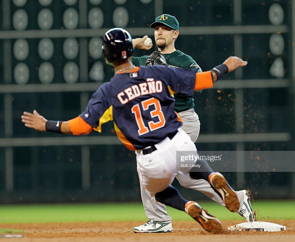 Jed Lowrie of the Oakland Athletics turns a double play as Ronny Cedeno of the Houston Astros attempts to break up the play at Minute Maid Park on...