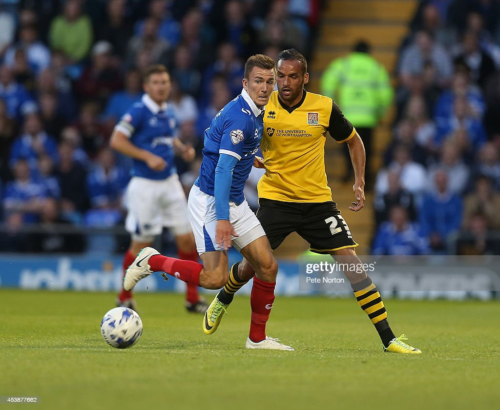 Jed Wallace of Portsmouth looks for the ball with Kaid Mohamed of Northampton Town during the Sky Bet League Two match between Portsmouth and Northampton Town at Fratton Park on August 19, 2014 in Portsmouth, England.