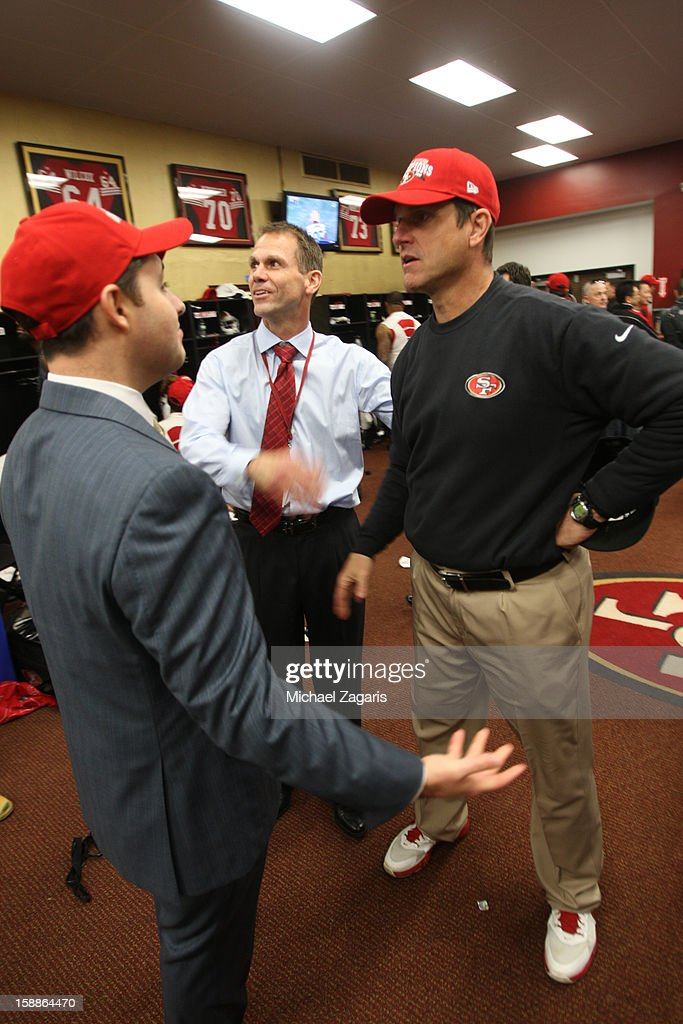 CEO Jed York of the San Francisco 49ers talks with General Manager Trent Baalke and Head Coach Jim Harbaugh in the locker room following the game against the Arizona Cardinals at Candlestick Park on December 30, 2012 in San Francisco, California. The 49ers defeated the Cardinals 27-13.