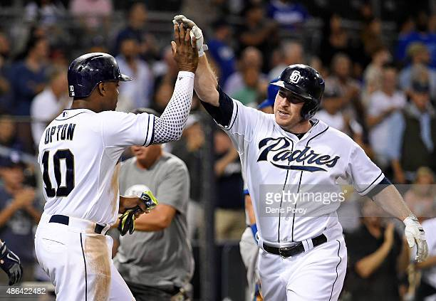 Jedd Gyorko of the San Diego Padres right is congratulated by Justin Upton after he hit a tworun home run during the eighth inning of a baseball game...