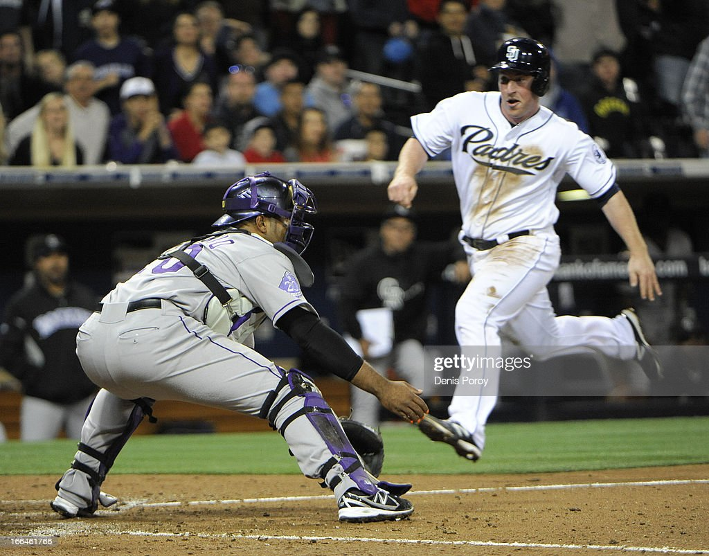 Jedd Gyorko #9 of the San Diego Padres scores ahead of the tag of <a gi-track='captionPersonalityLinkClicked' href=/galleries/search?phrase=Wilin+Rosario&family=editorial&specificpeople=5734314 ng-click='$event.stopPropagation()'>Wilin Rosario</a> #20 of the Colorado Rockies in the seventh inning of a baseball game at Petco Park on April 12, 2013 in San Diego, California.