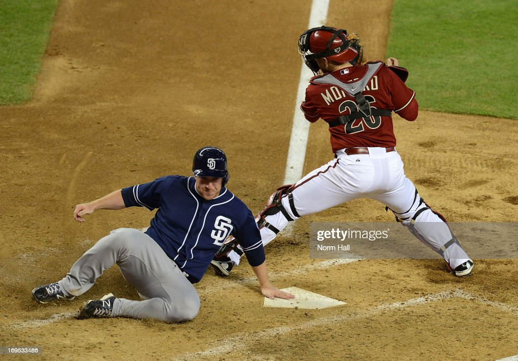 Jedd Gyorko of the San Diego Padres slides safely into home as Miguel Montero of the Arizona Diamondbacks attempts to block the plate at Chase Field...