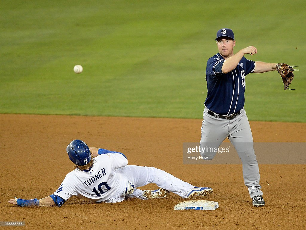 Jedd Gyorko #9 of the San Diego Padres turns a double play in front of Justin Turner #10 of the Los Angeles Dodgers during the seventh inning at Dodger Stadium on August 20, 2014 in Los Angeles, California.