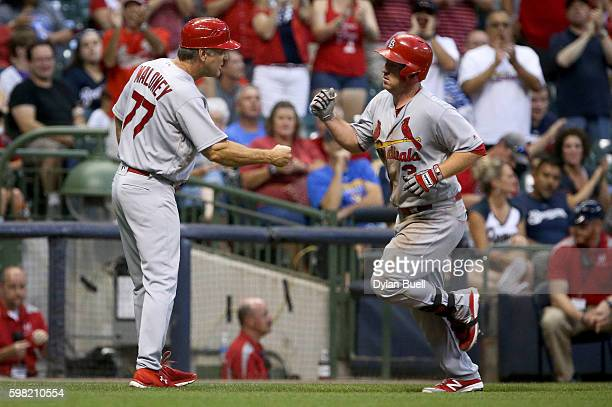 Jedd Gyorko of the St Louis Cardinals is congratulated by third base coach Chris Maloney after hitting a home run in the fifth inning against the...