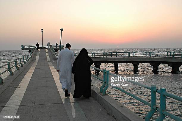 A woman in traditional black abaya with her male companion walks in the Corniche district in Jeddah Saudi men are very strict about their women's...