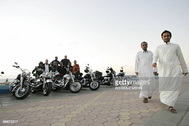 TO GO WITH AFP STORY BY SAM DAGHER Two Saudi men walk past a group of HarleyDavidson owners known endearingly as the 'Hoggies' on the Corniche of the...
