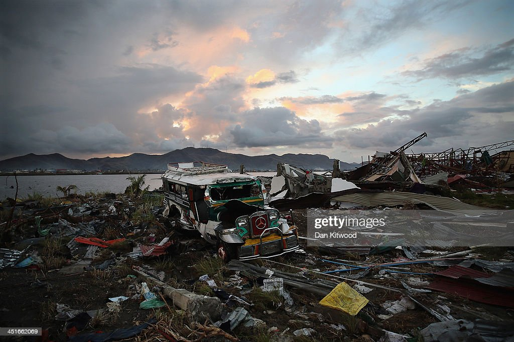 Jeepney smashed by Typhoon Haiyan lie amongst the debris in Tacloban on November 21 2013 in Leyte Philippines The Jeepney is a modified form of...