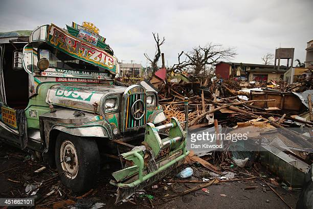 Jeepney smashed by Typhoon Haiyan lie amongst the debris in Tacloban on November 23 2013 in Leyte Philippines The Jeepney is a modified form of...