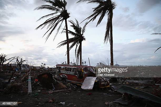 Jeepney smashed by Typhoon Haiyan lies amongst the debris in Tacloban on November 23 2013 in Leyte Philippines The Jeepney is a modified form of...