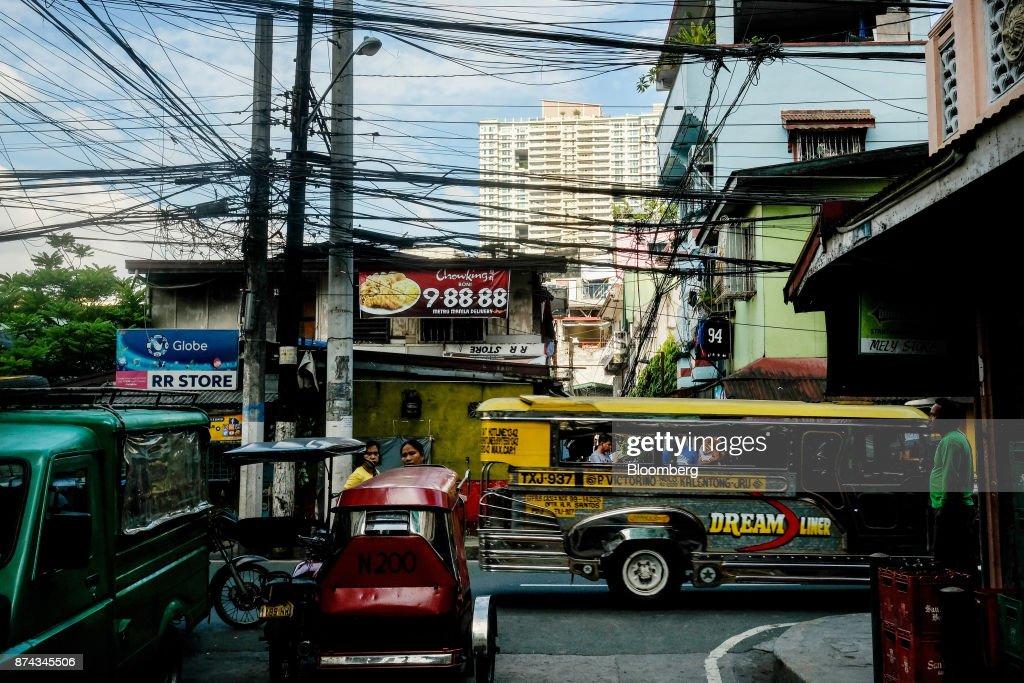 A jeepney travels past electricity cables in Mandaluyong, Metro Manila, Philippines, on Tuesday, Nov. 14, 2017. Economists are forecasting the Philippines to be among the first to raise interest rates in the region and the International Monetary Fund saidlast week the central bank should be ready to tighten if there are signs of overheating. Photographer: Veejay Villafranca/Bloomberg via Getty Images