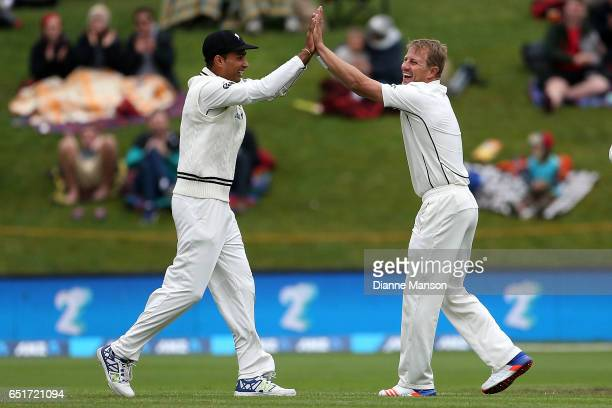 Jeet Raval and Neil Wagner of New Zealand celebrate the dismissal of Hashim Amla during day four of the First Test match between New Zealand and...